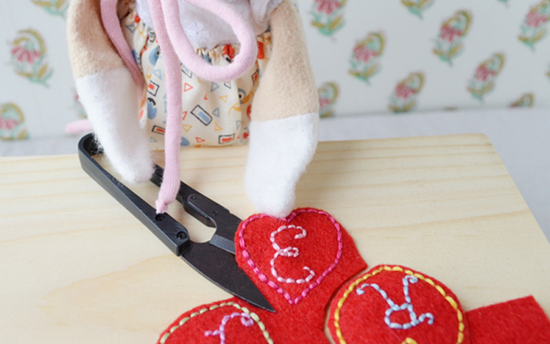 Once all the letters and hearts were embroidered, Lucy cut out the felt hearts. She was careful to stay a little bit outside the stitching so she wouldn't snip the threads.
