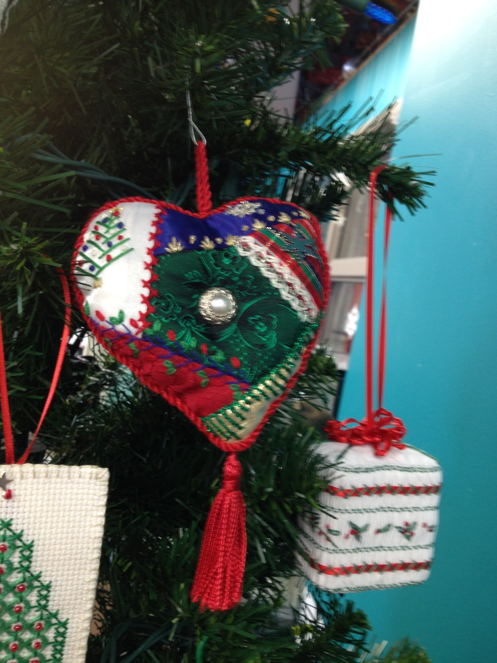 a crazy quilted ornament with twined piping and tassel