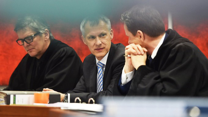 Ulrich Weiss, centre, flanked by his lawyers in German labour court