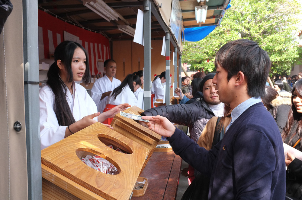 A man purchases Omikuji (Fortune-telling papers) at a local shrine in Okinawa, Japan.