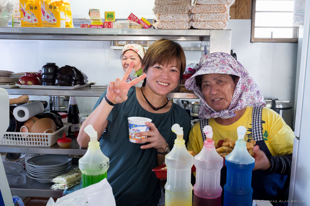 Two very kind ladies at a local (possibly the only) restaurant helping me decide on which Kakigori (shaved Ice) flavor to get.  Food was great too as I eat lunch there later. Fuji x100.