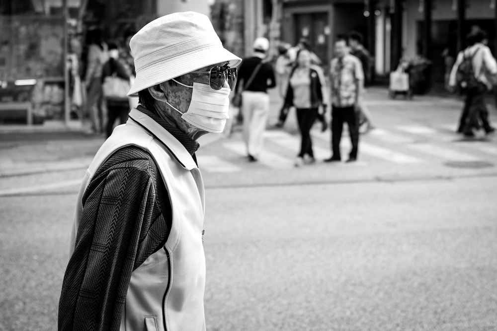 A man wearing a face mask, sunglasses and a hat walking on Kokusai street in Naha, Okinawa, Japan. Fuji x100s w/ TCLx100 Teleconverter at ISO200, f2.8, 1/500 sec.