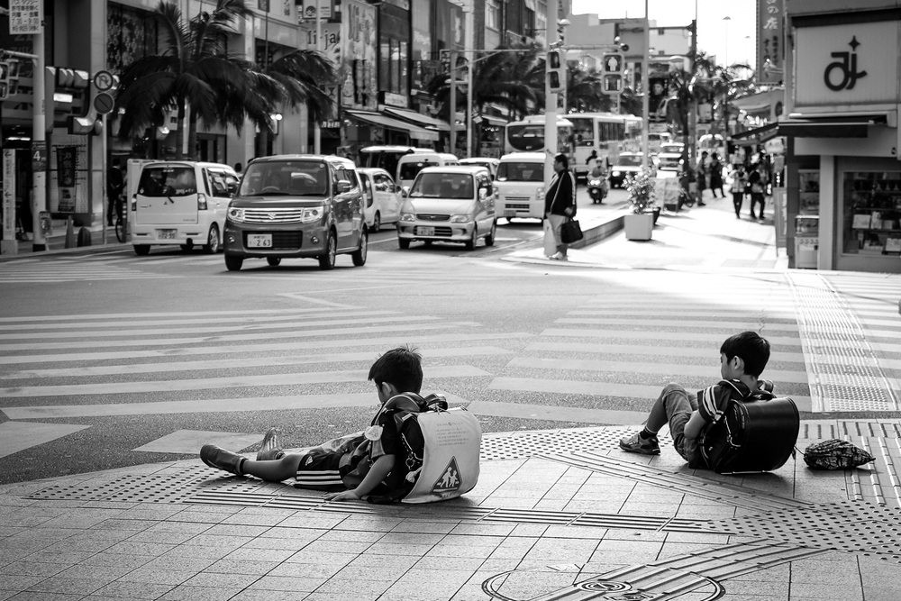 Two children take a break while waiting for the crosswalk in Naha, Okinawa, Japan. Fuji x100s w/ TCLx100 Teleconverter at ISO200, f2.8, 1/1250 sec.