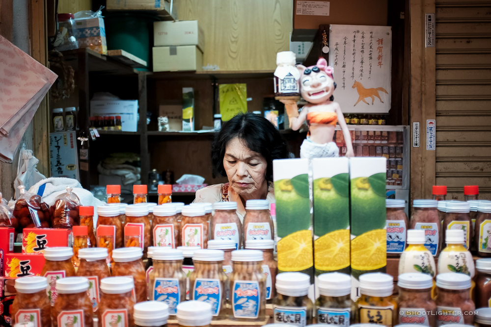 An Okinawan lady sells various jarred pickled products in Naha, Okinawa Japan. Fuji film x100T, ISO 320, f/2.0, 1/60 sec,  Fujifilm c  hrome film emulation,  edited in Adobe Lightroom 6.