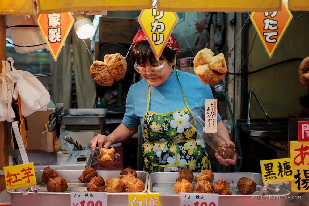 An Okinawan lady sells Sata Andagi (Okinawan style doughnuts サーターアンダーギー) in Naha, Okinawa Japan. Fujifilm x100T, ISO 400, f/2.0, 1/320 sec,  Fujifilm c  hrome film emulation , edited in Adobe Lightroom 6.