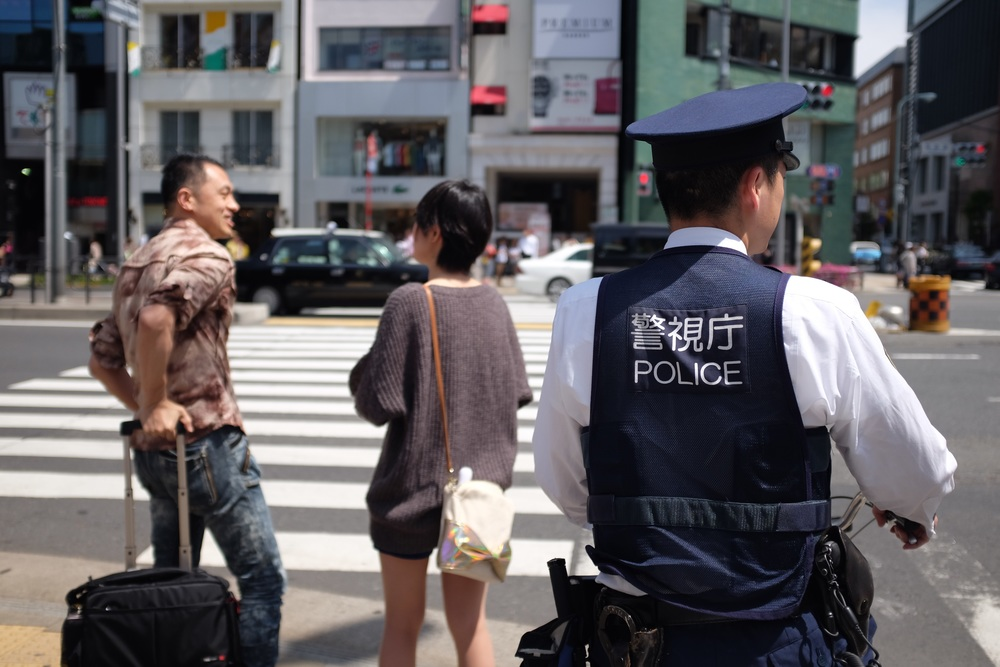 A policeman waits to cross at Aoyama dori near Omotesando station, Tokyo. Fujifilm x100t, ISO 200, f/2, 1/600 sec. ND filter on. No edit, straight out of camera.