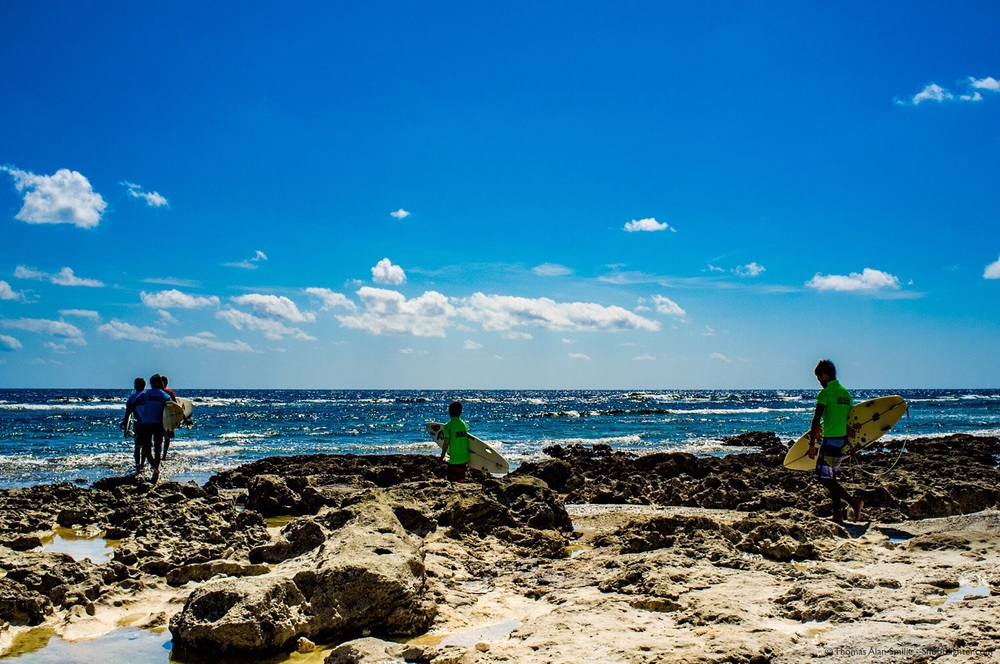 Surfers in Okinawa, Japan head out in search of waves to ride. Fujifilm x100 1/500 sec, f/11, ISO 200. Edited in Adobe Lightroom.