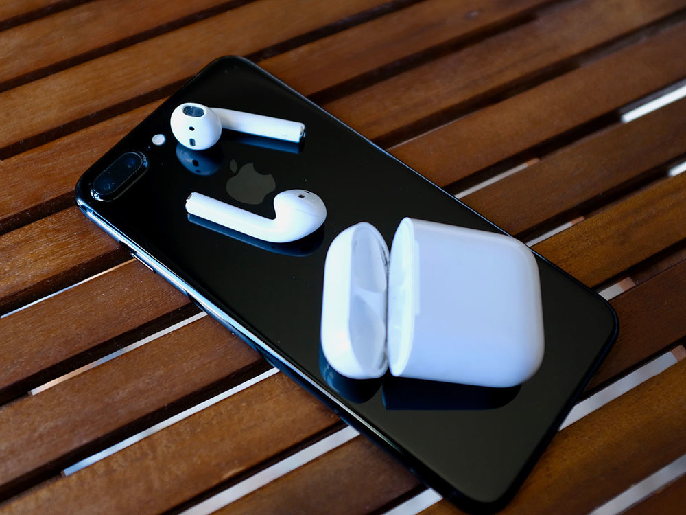 Apple AirPods 1 and charging case on an iPhone 7 Plus Jet Black.