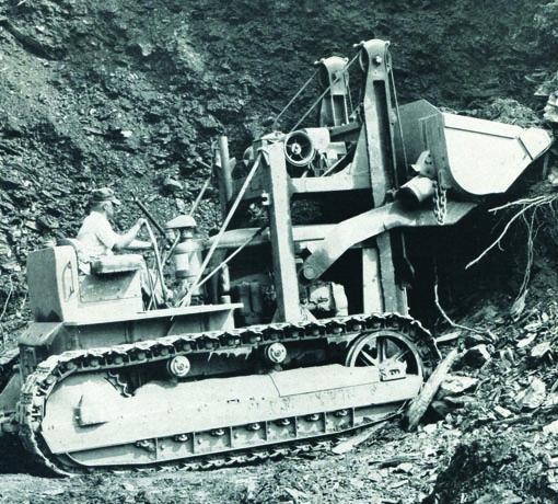 Fabriqué par Trackson Corp à Milwaukee dans le Michigan (USA), ce chargeur frontal hydraulique de +/-8 t était monté sur un tracteur sur chenilles Caterpillar D4. Il était propulsé par un moteur diesel 4 cylindres développant 43HP. Par un savant jeu de bras et biellettes, deux paires de vérins hydrauliques fixés au bâti monté sur un tracteur actionnent un bac de chargement ou une lame pour pousser et niveler. La cabine artisanale se fermait par des toiles rabattantes fixées au toit en taule ondulée. Lorsque Caterpillar a repris Trackson en 1951, ce modèle HT a continué à être fabriqué: seul le nom sur le bouclier avant a alors été changé. Date de construction : 1952     Traxcavator Caterpillar 955