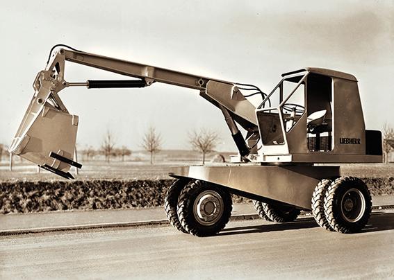 En 1954, Hans Liebherr lance sa première pelle sur pneus L 300 un nouveau type d'engin de 7,5 tonnes dotée d'un châssis en «Y » et de 6 pneus jumelés. Elle était propulsée par un moteur Deutz de 25ch. C'est la première fois qu'une machine de construction est pourvue d'une cabine de conducteur, d'un bras réglable et d'une combinaison godet frontal/godet rétro. Sa couronne de rotation est le fruit d'un travail de développement et d'une production assurée en interne. La transmission est encore mécanique. Une deuxième innovation de taille suit peu de temps après : en 1960, Liebherr lance avec la pelle sur pneus A 650 la première pelle sur pneus entièrement hydraulique, c'est-à-dire dotée aussi d'une transmission hydraulique en plus de l'équipement de travail hydraulique. Avec un poids en ordre de marche de 16 tonnes, cette machine dispose d'une puissance de 60 ch et marque une étape importante dans l'histoire des pelles sur pneus. En 1967, le constructeur lance une pelle rail-route. 1983 voit apparaître la pelle sur pneus A912 de 17t équipée d'une transmission hydrostatique et propulsée par un moteur Deutz développant 95ch. Quelques années plus tard, en 1989, Liebherr équipe ses pelles du système Litronic qui allie une électronique intelligente et une hydraulique fonctionnelle pour contrôler, commander, réguler et coordonner tous les systèmes importants de la pelle. C'est la pelle A 912 Litronic qui en a été équipée la première.      La bonne coopération entre la machine et son outil joue un rôle essentiel pour un travail idéal sur le terrain    .