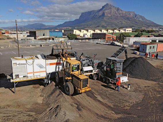 Les travaux ont été réalisés par Power Construction en coopération avec Milling Techniks, qui a pris en charge la production de l'enrobé MSB avec le mélangeur de recyclage à froid KMA 200 de Wirtgen. Pendant la durée du chantier, le fraisât d'enrobé stocké a été envoyé pour essai technique à Durban dans des laboratoires pour MSB. La composition de l'enrobé a été déterminée au moyen de trois différentes formules en utilisant le fraisât d'enrobé de deux gisements que la ville avait spécialement affectés à ce projet. La structure de la chaussée pouvait donc être réalisée dans les variantes suivantes :  100% de fraisât d'enrobé  ,100% de fraisât d'enrobé mélangé à 10% de poussière de concassage   100% de fraisât d'enrobé mélangé à 25% de gravier naturel   À partir des résultats d'essai, la variante la plus rentable pour la pose de la couche MSB 1 s'est avérée être une composition d'enrobé à partir de 100% de fraisât d'enrobé avec une adjonction de 2,1% de mousse de bitume et de 1% de ciment.   Le mélangeur Wirtgen a été installé dans l'entrepôt de Ndabeni Roads and Stormwater à Maitland. Cet entrepôt offrait suffisamment de place pour installer le KMA 220 et assurer le stockage intermédiaire du fraisât non traité, du fraisage criblé et de l'enrobé MSB produit. Le fraisât d'enrobé criblé a été transformé par le mélangeur KMA 220 en enrobé MSB 1, puis temporairement stocké dans l'entrepôt sur une période allant jusqu'à 7 jours. Afin de garantir l'excellente qualité de l'enrobé BSM ainsi que l'homogénéité du processus d'enrobage, Power Construction, Milling Techniks et WorleyParsons ont élaboré un système d'assurance qualité spécialement adapté à la production de MSB au moyen du mélangeur de recyclage à froid, l'objectif étant de satisfaire ainsi aux exigences MSB 1 sur toute la durée du projet. Une fois l'enrobé produit, le matériau était soit immédiatement posé sur le chantier, soit bâché et temporairement stocké dans l'entrepôt de Ndabeni. L'enrobé MSB a été posé en une