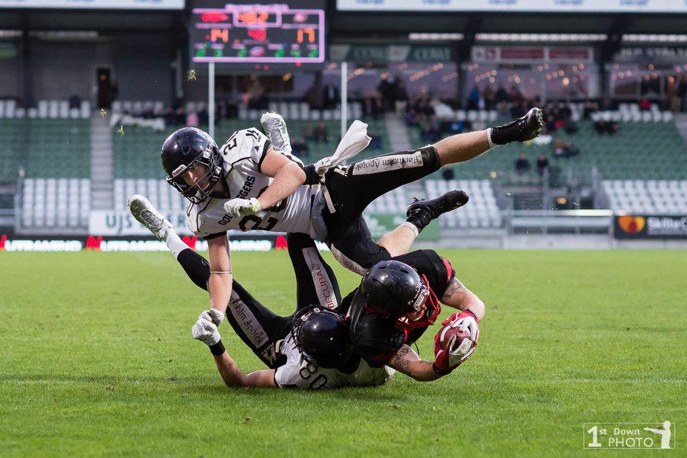 Mikkel Lindsø og Jonas Bo Hansen tackler Vejles Geoffrey Lewis. - Photo af 1st Down Photo.