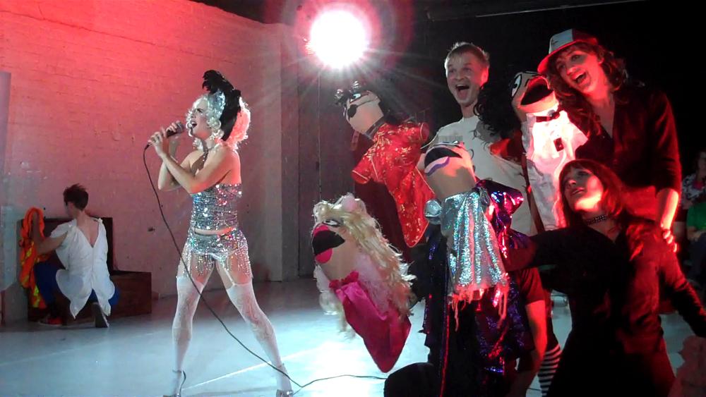 [Screen Capture]  Trixxie Carr (Tiny Dionysus), Stanley Frank (Chorus), Steve Fishell (Chorus), Joshua Thake (Chorus), Audra Wolfmann (Chorus).    Scenic Design by Maya Linke and Ben Randle, Lighting Design by Anthony Powers.
