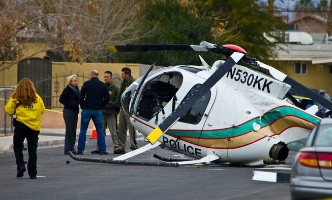 A damaged Las Vegas Metro Police MD530F helicopter sets on 23rd St in Las Vegas after pilot was forced to make an auto-rotational landing. Photo Credit LE Baskow Las Vegas Sun