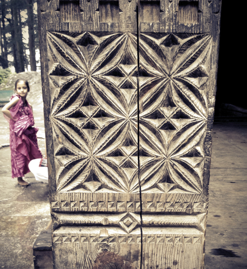 Detail of pillar carvings and young girl at the temple entrance