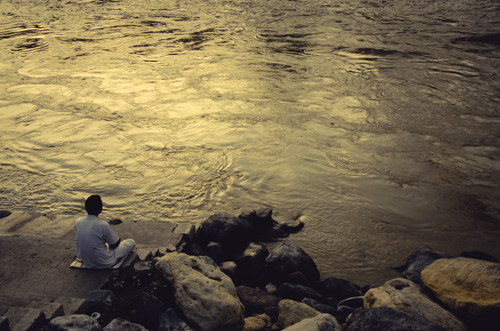 A man meditates in the evening by the river