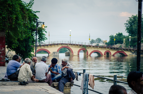 A group of men playing cards by the lake, and the Rialto-like bridge in the background