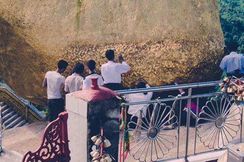 Pilgrims pressing gold leaf on to the sacred boulder.