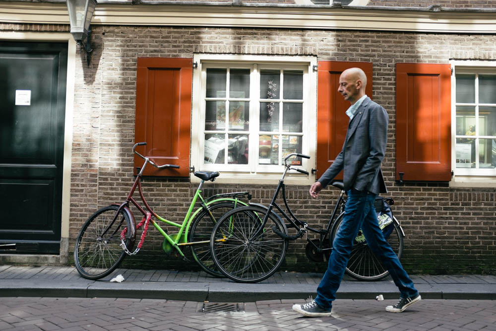 Very Dutch looking man walking into the beautifully lit little section of a back alley.