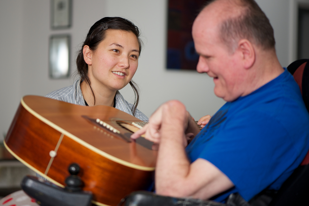 woman looking at man with a disability play guitar.jpg