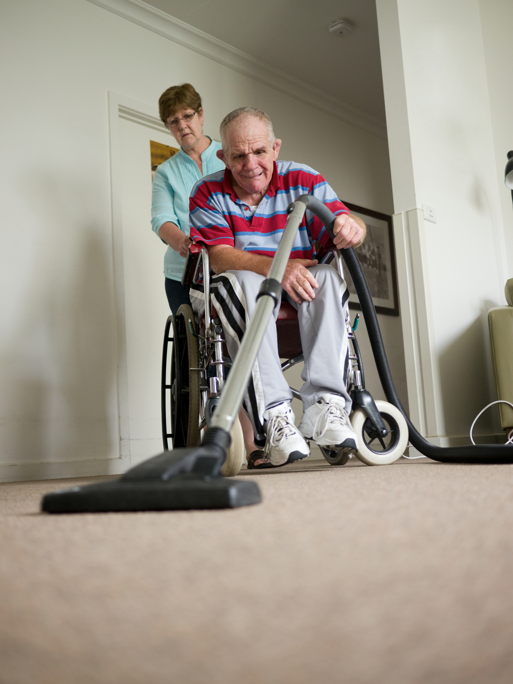 sixty-six year old man with a disability vacuuming.jpg