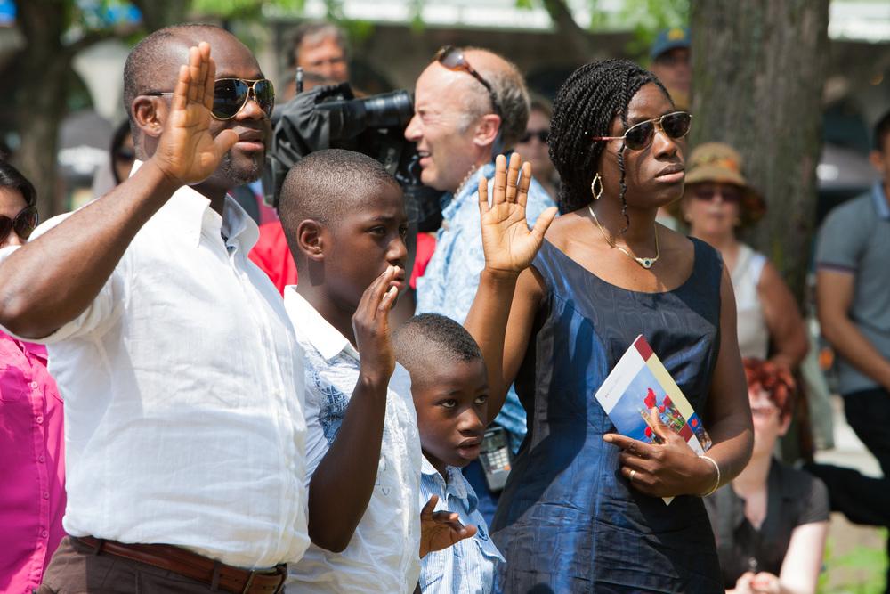 Une famille de nouveaux citoyens prêtent serment lors de la cérémonie.