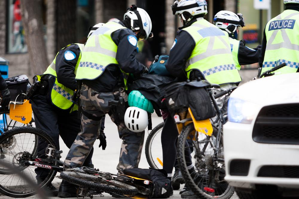 Manifestante à vélo arrêtée par des policiers.