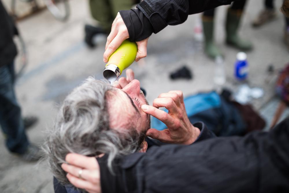 Un journaliste citoyen reçoit les premiers soins après avoir été aspergé en plein visage de poivre de cayenne au pavillon des sciences de l'UQAM.