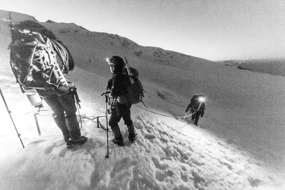 Climbing up the Easton Glacier by headlamp. Note the slushy snow and deep prints; alpine starts are meant to avoid those issues. Encountering them this early is a bad sign.