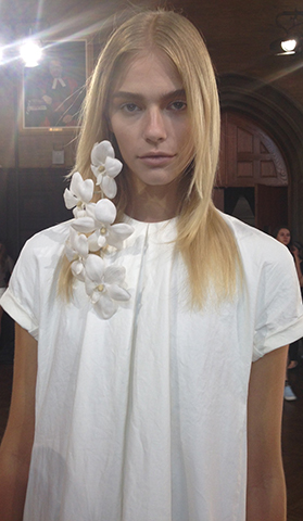 "Lead Hair Stylist: Amy Friadd for Kate Ryan Inc.  For Kaelen's tropical-inspired Spring/Summer 2015 collection, hairstylist Amy Farid created a clean and innocent look from the '70s with a nod to hair icon Marcia Brady. ""We wanted that freshly washed, really brushed hair,"" explained Farid. ""Like how Marcia Brady would brush her hair 100 times before bed."" Farid also made sure to keep the models' hair tucked behind their ears. Before the presentation, the hair framing the model's face would show off a natural bend around the cheekbone. Some models also wore a hair clip with fresh orchids on it.  Photo Courtesy of Oribe Hair Care"