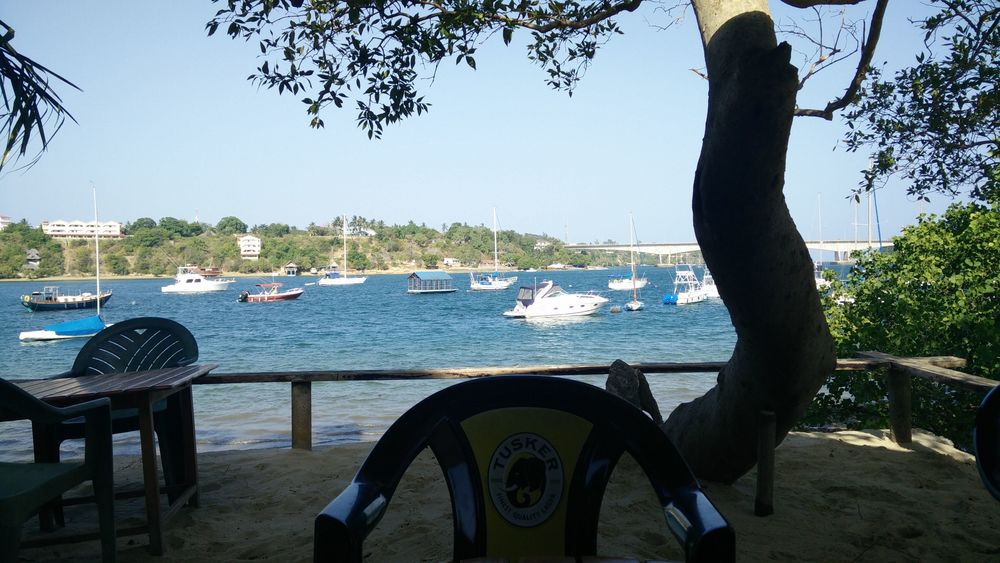Kilifi Bridge in the background (split into two by the tree in front of the Tusker seat).