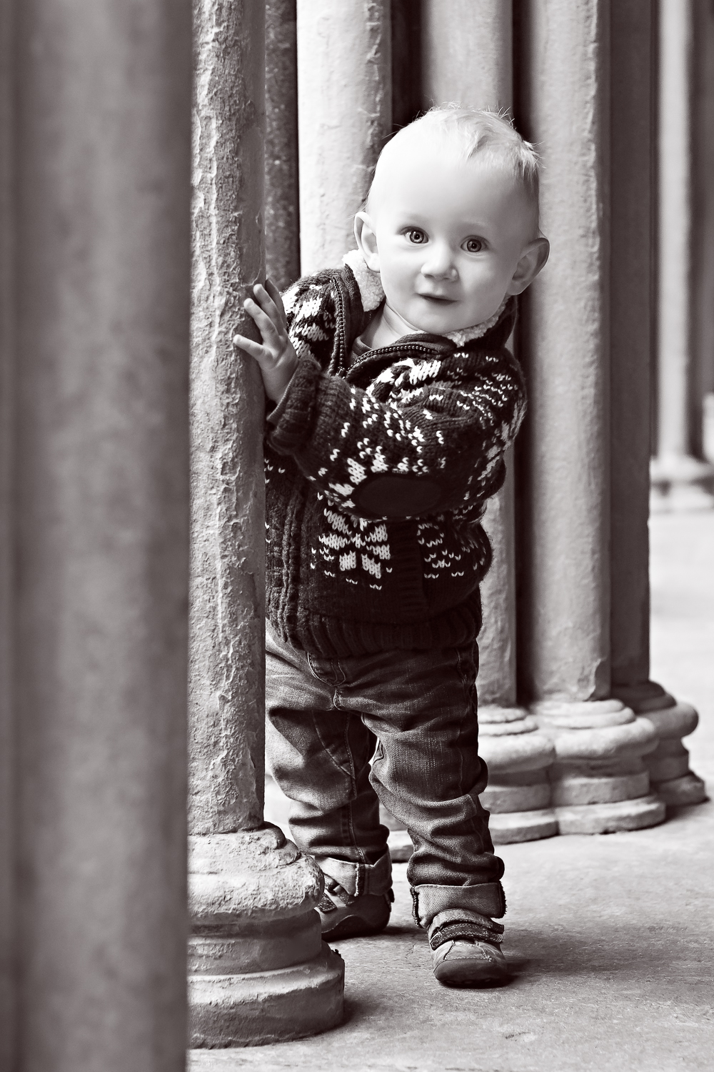 Black and white photograph of a little boy peaking his head around one of the cloisters at Salisbury Cathedral grounds