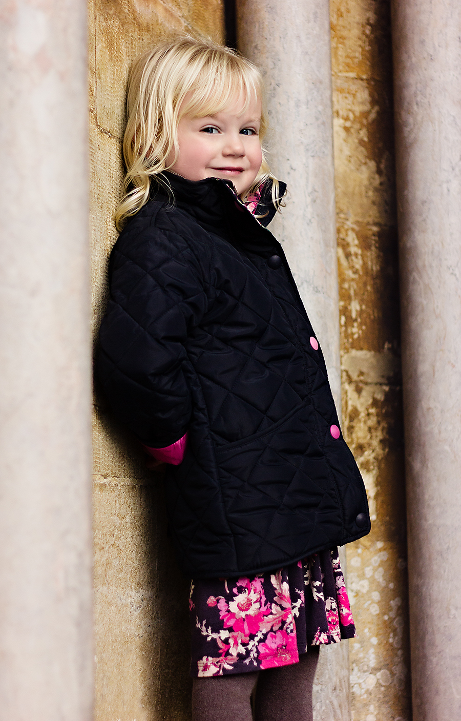 Blonde girl leaning against Salisbury Cathedral wall, looking over at the camera