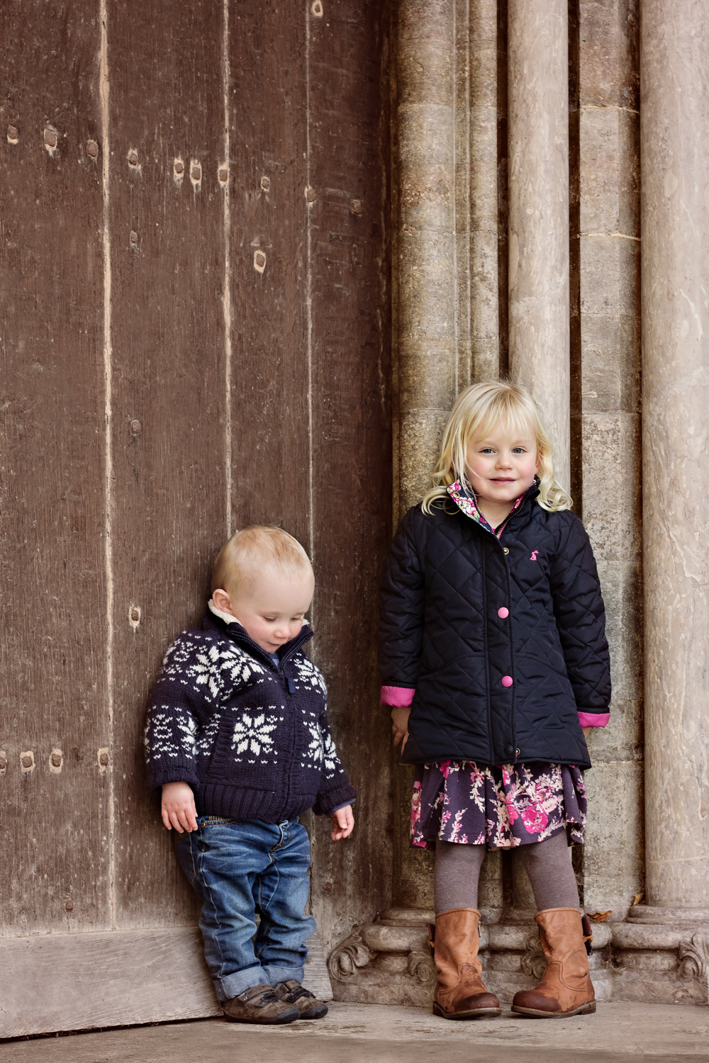 Little Brother and older sister stand against a big brown wooden door at Salisbury Cathedral - the boy looks down and the girl looks at the camera