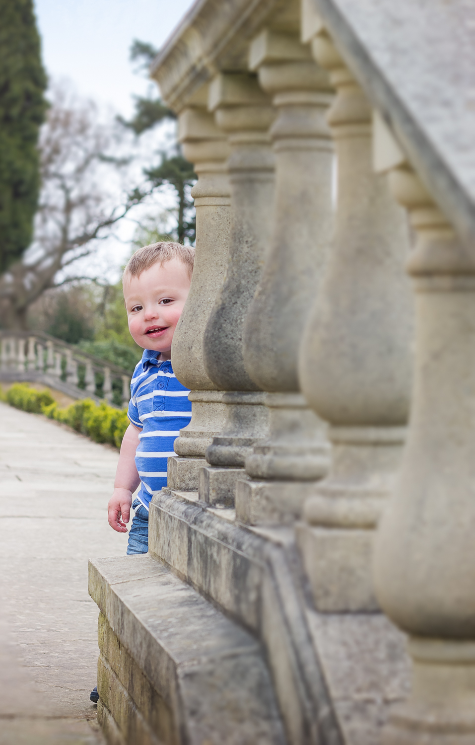 Two year old child photography session shows the little boy peeking around the corner of the stone balustrades