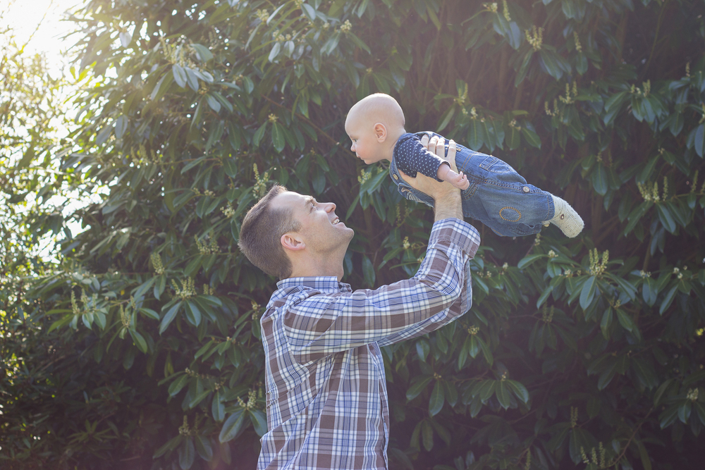 Father raises his baby son in the air at the park