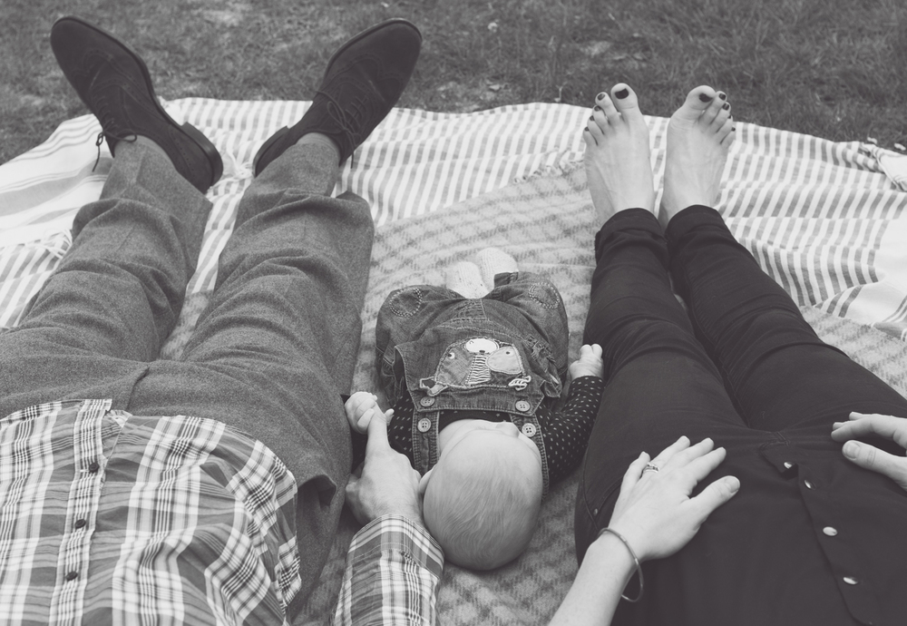 Fine art image of parents and baby boys legs and feet on a blanket in black and white