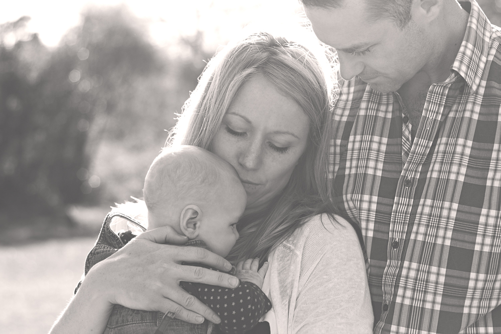 Fine art black and white portrait of a Mum, Dad and baby boy on a family day out