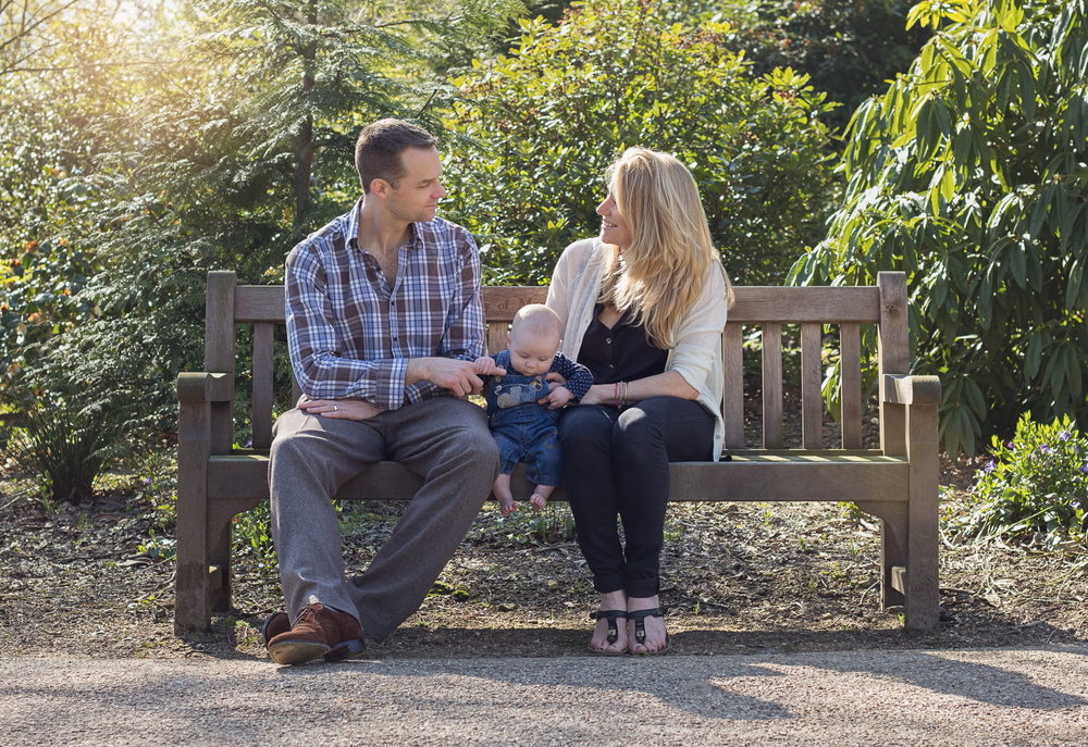 Mama and Dad sitting on a bench in Tunbridge Wells looking down at the happy little 3 month old boy