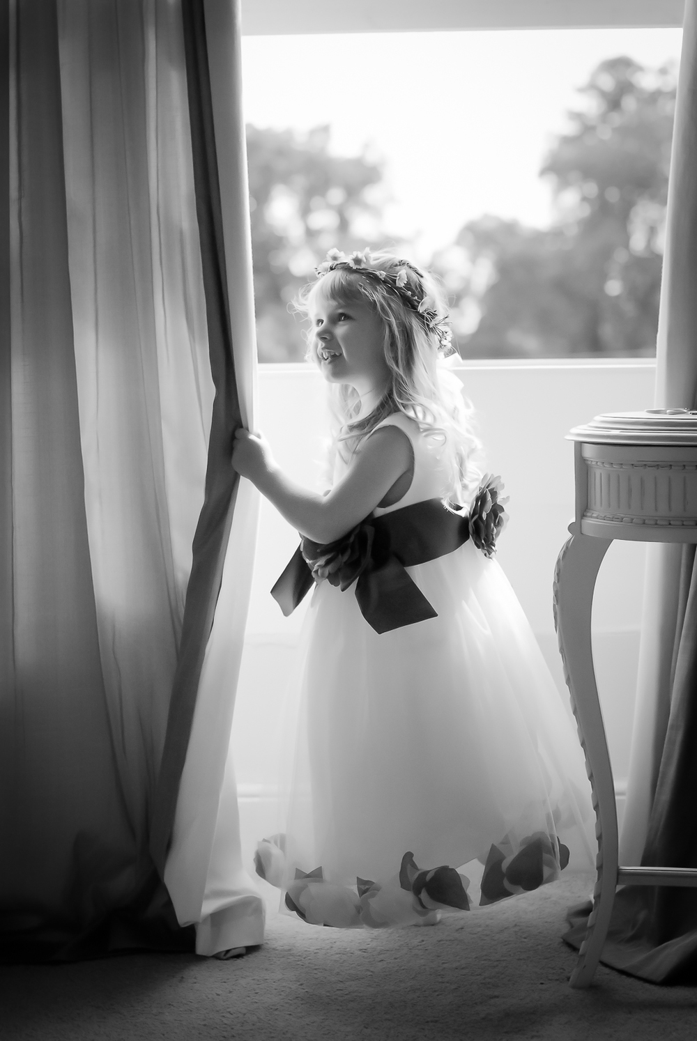 Black and white wedding photo of a child bridesmaid leaning on a curtain and smiling across