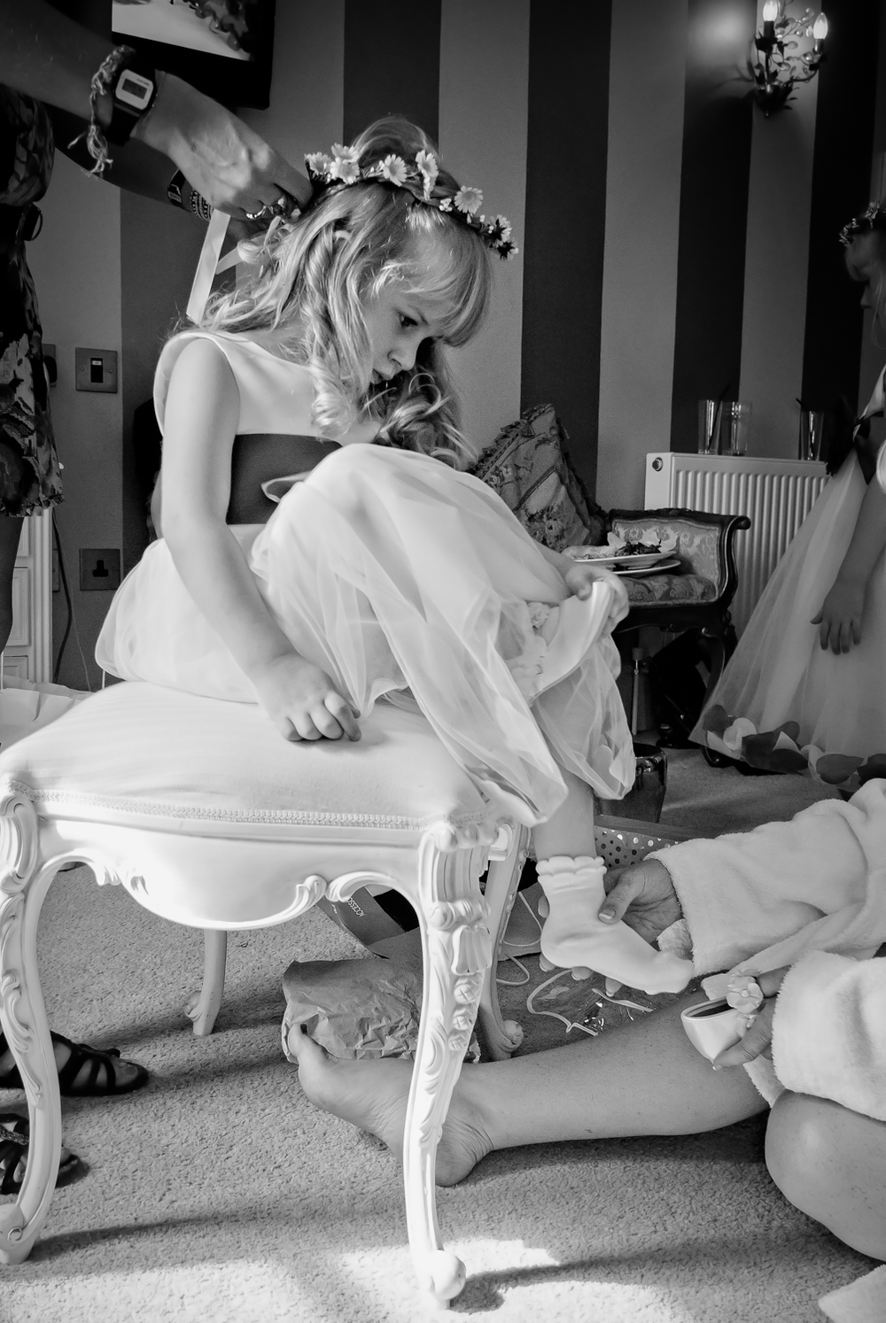 Professional wedding photograph of a child bridesmaid sat on a chair having her shoes put on by her mum