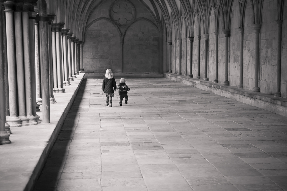 Fine art black and white image of a big sister and her little brother walking into the distance at the cloisters in Salisbury.
