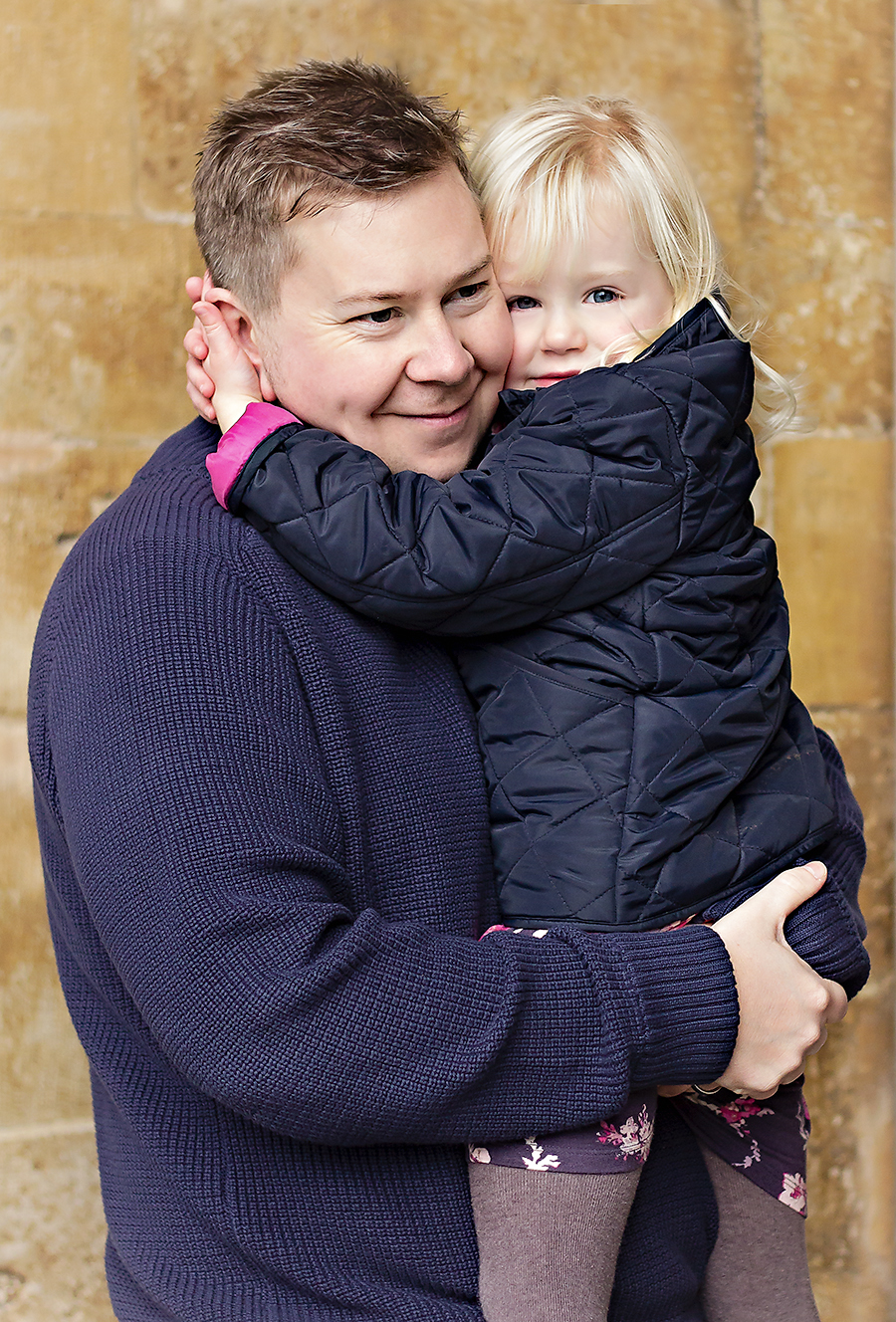 Close-up image of a Dad wearing a big blue jumper and his young daughter outside the entrance to the Cathedral