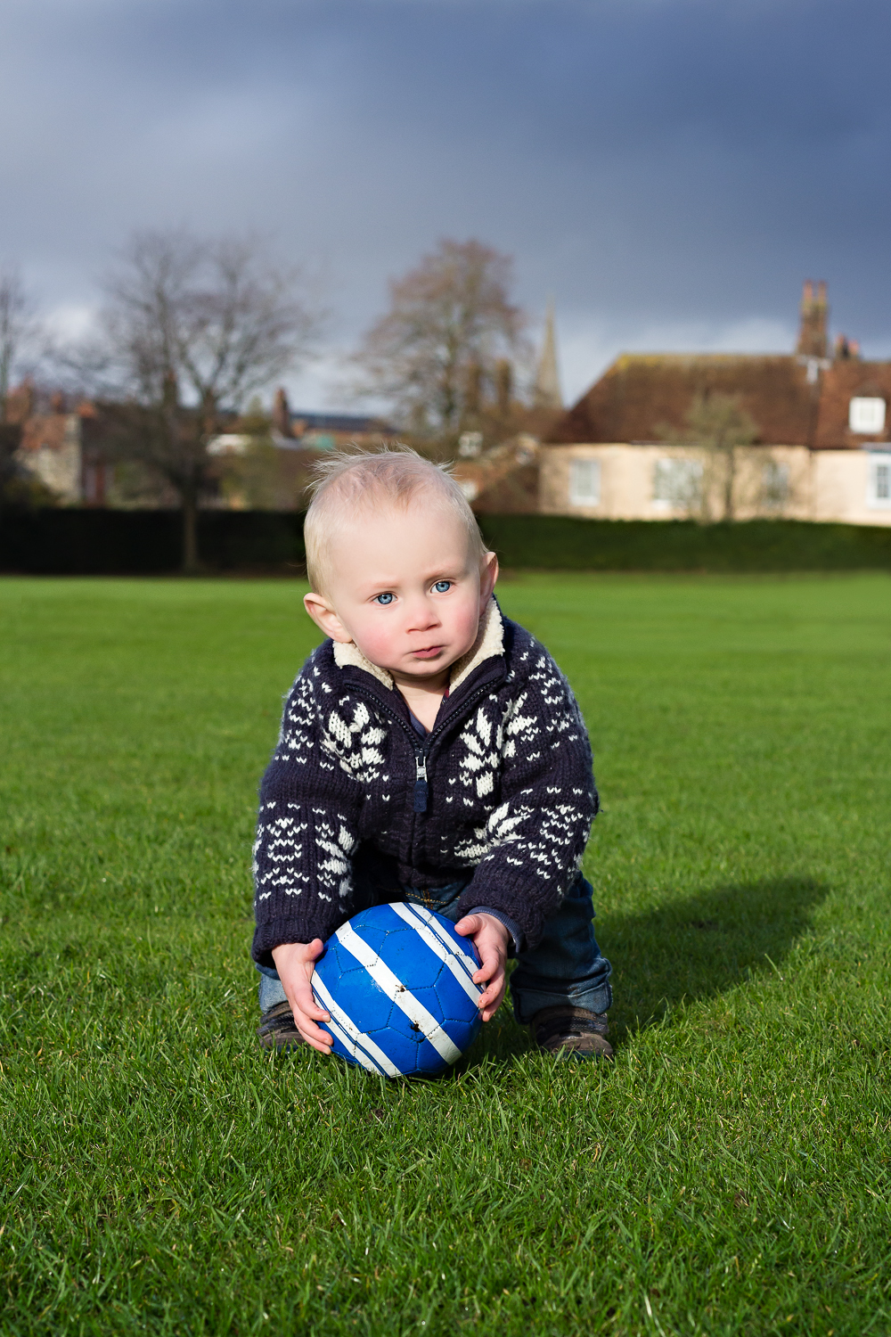 A little boy in a Christmas snowflake jumper leans down to pick up a football, with thundery clouds in the background.