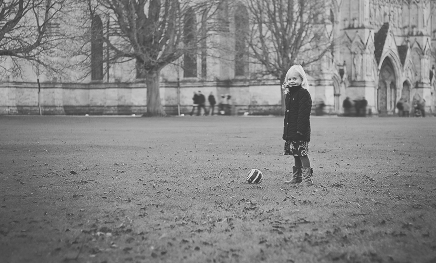 Little girl playing football during a family photography session at Salisbury Cathedral Grounds