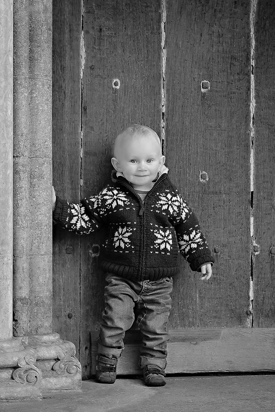 Black and white image of a 3 year old boy leaning against a stone column at Salisbury Cathedral