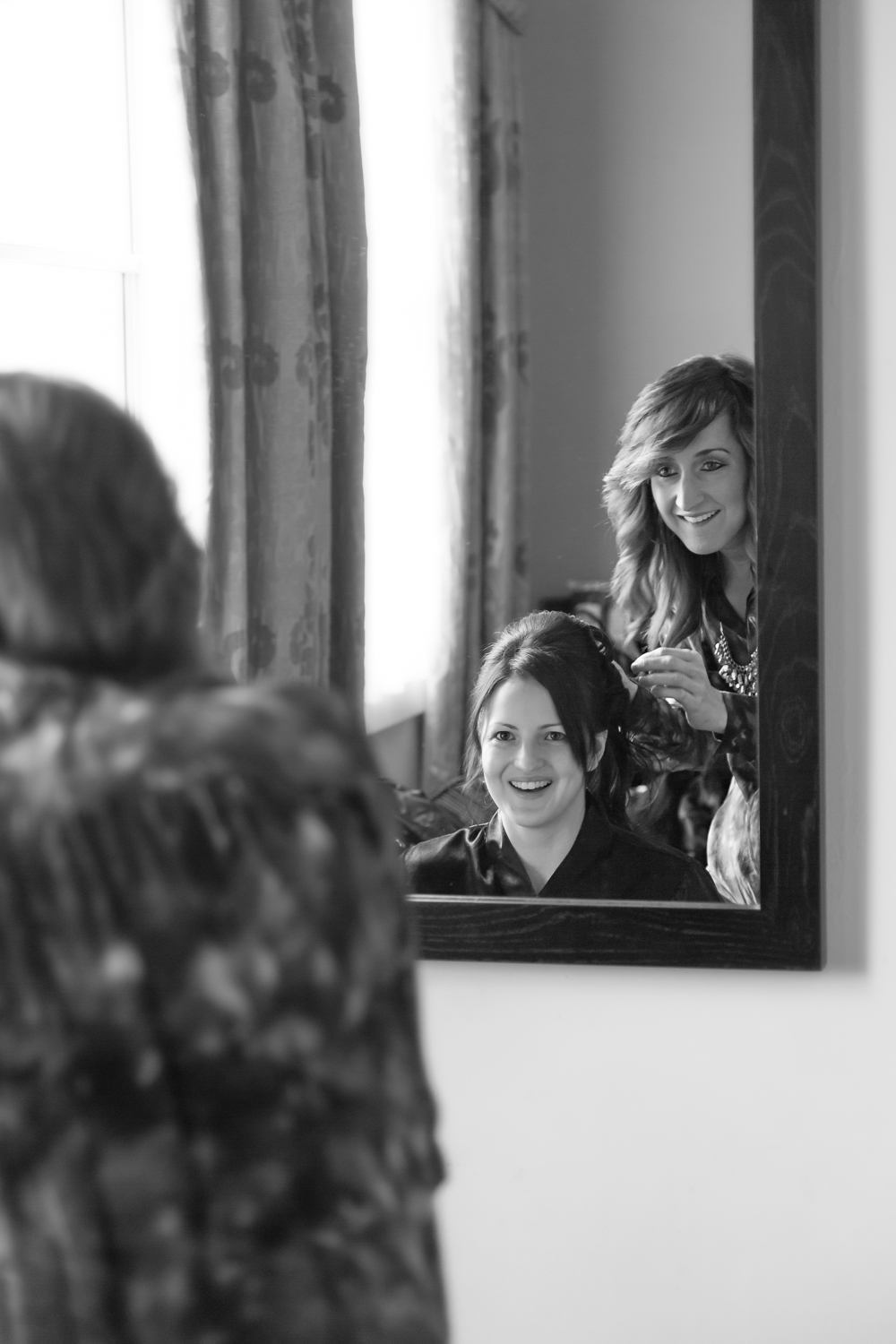 Photograph of a bride and hairdresser looking into the mirror smiling