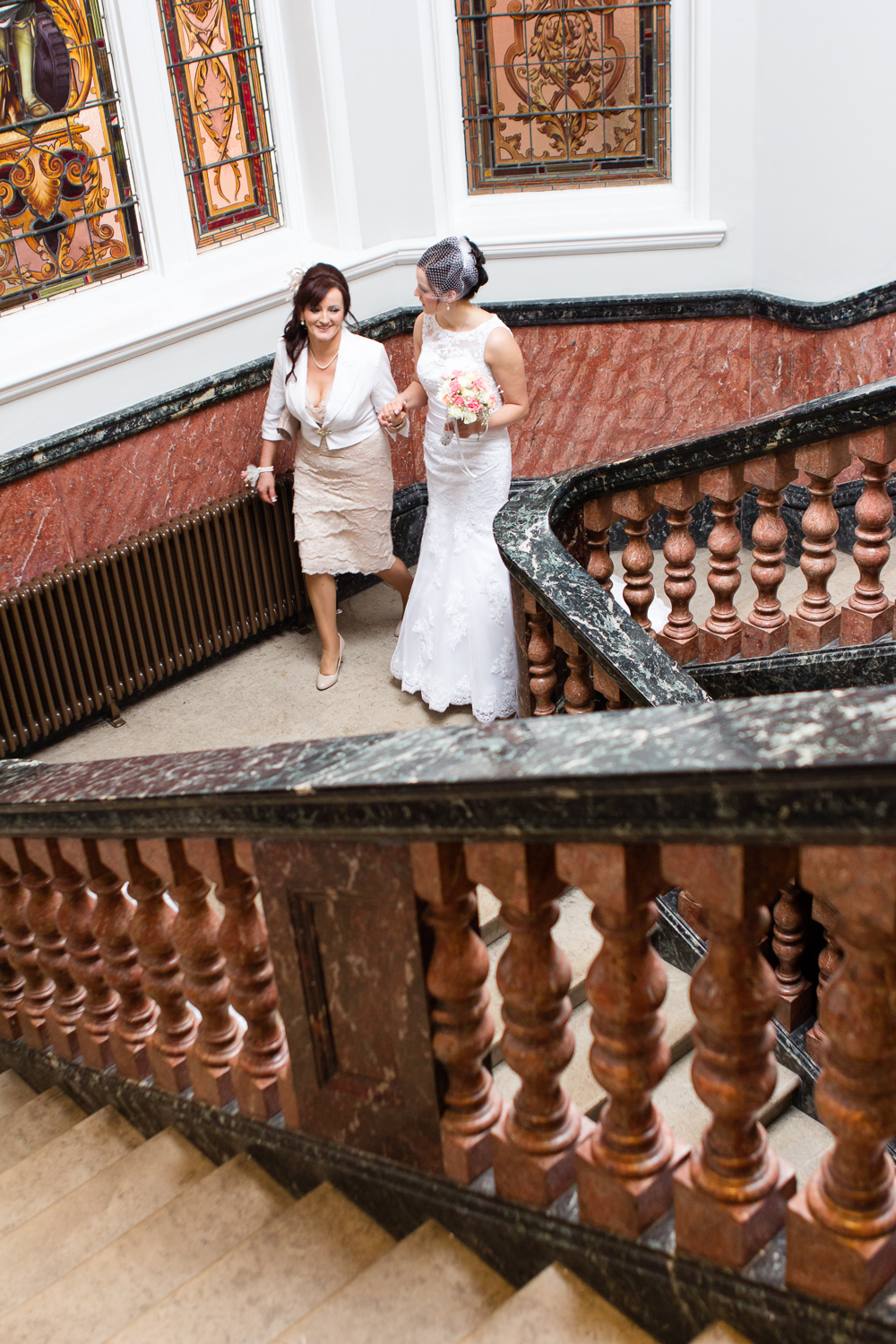 Wedding photography in Kingston - the bride and her mum walk down the hotel staircase, on their way to the church