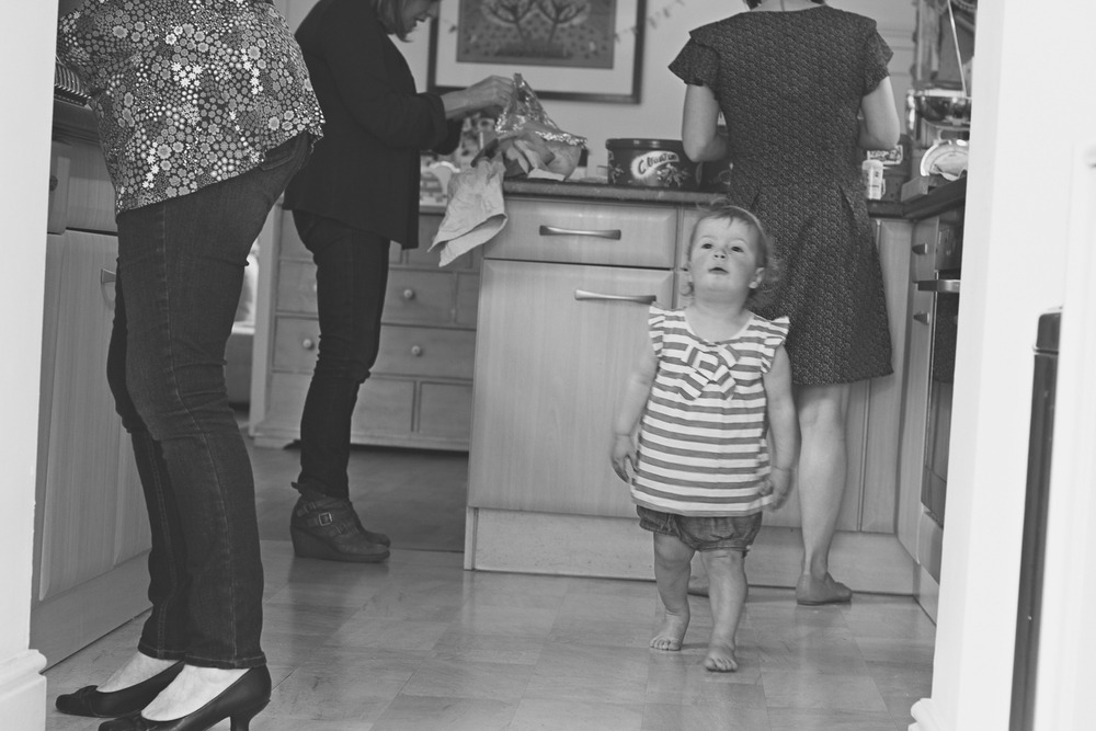 Three generations of women photographed in the kitchen, as Mum and two grandma's work preparing party food, the two-year-old birthday girl walk through the kitchen amid the chaos