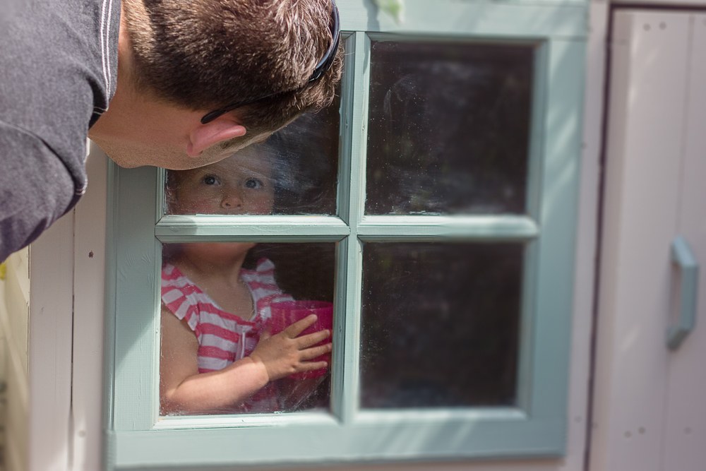 An uncle peers in to the wendy house to see his neice playing happily